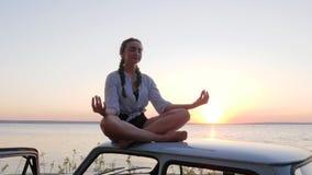 Κοριτσιών στο αυτοκίνητο στεγών υπαίθρια, θηλυκή περισυλλογή στο ηλιοβασίλεμα στο αυτοκίνητο στη θάλασσα υποβάθρου σε σε αργή κίν απόθεμα βίντεο