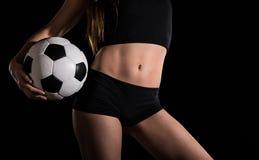 Κορμός μιας προκλητικής γυναίκας με ένα ποδόσφαιρο στοκ φωτογραφία