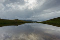κορσικανικά βουνά βουνών λιμνών λάκκας creno de Γαλλία της Κορσικής σκοτεινός δραματικός σύν&nu χρυσό ύδωρ επιφάνειας κυματώσεων Στοκ Εικόνα