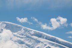 Κορυφή ενός βουνού χιονιού με το μπλε ουρανό Στοκ Φωτογραφίες