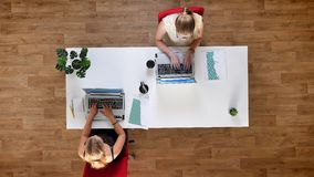 Κορυφή κάτω από τον πυροβολισμό, δύο εργατικά θηλυκά που στα lap-top τους και που κάθεται στον πίνακα στο ξύλινο στούντιο απόθεμα βίντεο