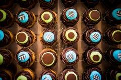 Κορυφή κάτω από τον πυροβολισμό της ζωηρόχρωμης μπλε και κίτρινης σοκολάτας cupcakes στοκ φωτογραφίες