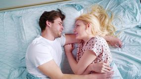 Κορυφή κάτω από το ζουμ στο νέο χαμογελώντας ζεύγος στο κρεβάτι το πρωί απόθεμα βίντεο