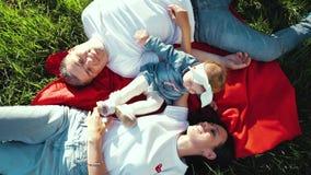 Κορυφή κάτω της ευτυχούς οικογένειας με να βρεθεί κορών μικρών παιδιών στο κάλυμμα στο θερινό πάρκο απόθεμα βίντεο