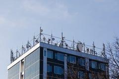 Κορυφή της οικοδόμησης του συνόλου των δορυφόρων και των συνδέσεων μικροκυμάτων - παραμονή που συντονίζεται στοκ εικόνες