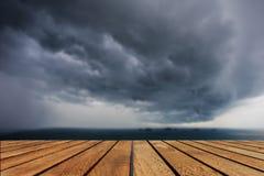 Κορυφή του ξύλινου πίνακα και των σκοτεινών σύννεφων πέρα από τη θάλασσα Στοκ φωτογραφία με δικαίωμα ελεύθερης χρήσης