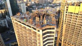 Κορυφή του υψηλού κτηρίου πύργων με τους εργαζομένους στο εργοτάξιο οικοδομής Μεγάλη ανάπτυξη πόλεων μητρόπολη εναέρια όψη φιλμ μικρού μήκους