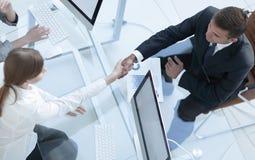 κορυφαία όψη χειραψία ο ανώτερος διευθυντής και ο υπάλληλος επάνω από το γραφείο Στοκ Εικόνες