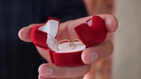 Κοσμήματα για την αγαπημένη γυναίκα του ο νεόνυμφος κρατά στο κιβώτιο χεριών χρυσών γαμήλιων δαχτυλιδιών του closeup χρυσή διακόσ φιλμ μικρού μήκους