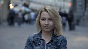 Κοσμοπολίτικο όμορφο ξανθό κορίτσι χωρίς το makeup στην οδό και το υπόβαθρο ανθρώπων απόθεμα βίντεο