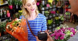 Κοστούμι που κάνει την πληρωμή μέσω της πιστωτικής κάρτας στο ανθοπωλείο απόθεμα βίντεο