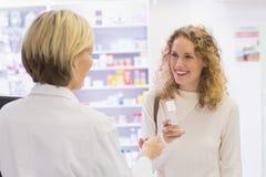 Κοστούμι που παρουσιάζει βάζο ιατρικής στο φαρμακοποιό στοκ φωτογραφία με δικαίωμα ελεύθερης χρήσης