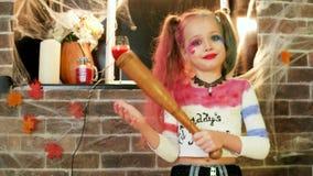 Κοστούμι του Harley quinn αποκριές, μικρό κορίτσι που παίζει τον τρελλό χαρακτήρα, εορτασμός κομμάτων αποκριών απόθεμα βίντεο