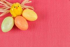 Κοτόπουλο Πάσχας με τα χρωματισμένα αυγά σε ένα ρόδινο κατασκευασμένο υπόβαθρο στοκ εικόνα