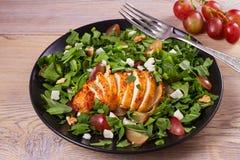 Κοτόπουλο, σταφύλια και σαλάτα τυριών αιγών στο μαύρο πιάτο στο ξύλινο υπόβαθρο Στοκ Εικόνες