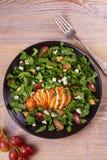 Κοτόπουλο, σταφύλια και σαλάτα τυριών αιγών στο μαύρο πιάτο στο ξύλινο υπόβαθρο Στοκ εικόνα με δικαίωμα ελεύθερης χρήσης