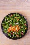 Κοτόπουλο, σταφύλια και σαλάτα τυριών αιγών στο μαύρο πιάτο στο ξύλινο υπόβαθρο Στοκ φωτογραφίες με δικαίωμα ελεύθερης χρήσης