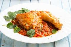 Κοτόπουλο στη σάλτσα ντοματών και τα φρέσκα χορτάρια στοκ εικόνες