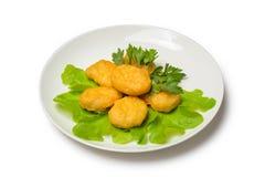 Κοτόπουλο nagets με το μαρούλι σε ένα πιάτο σε ένα άσπρο υπόβαθρο Στοκ εικόνα με δικαίωμα ελεύθερης χρήσης