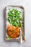 Κοτόπουλο ή χοιρινό κρέας schnitzel με το τυρί και τη σαλάτα μπιζελιών στοκ φωτογραφίες