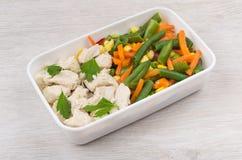 Κοτόπουλο με τα λαχανικά και μαϊντανός στο πλαστικό εμπορευματοκιβώτιο στο tabl Στοκ εικόνα με δικαίωμα ελεύθερης χρήσης