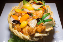 Κοτόπουλο με τα καρύδια των δυτικών ανακαρδίων στην τριζάτη Taro φωλιά Στοκ Εικόνες