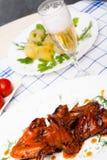Κοτόπουλο που ψήνεται στη σχάρα με τις βρασμένες πατάτες και που μαρινάρεται tomatoe Στοκ φωτογραφία με δικαίωμα ελεύθερης χρήσης
