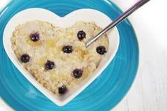 Κουάκερ ή Oatmeal βακκινίων σε ένα διαμορφωμένο καρδιά κύπελλο Στοκ φωτογραφία με δικαίωμα ελεύθερης χρήσης
