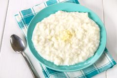 Κουάκερ γάλακτος ρυζιού με τα καρύδια και τις σταφίδες σε ένα μπλε πιάτο σε ένα whi στοκ φωτογραφία με δικαίωμα ελεύθερης χρήσης