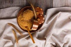 Κουάκερ καλαμποκιού σε ένα ξύλινο πιάτο με τις ακίδες σίτου σε ένα ύφασμα σε έναν πίνακα κινηματογραφήσεων σε πρώτο πλάνο Στοκ Φωτογραφία