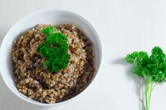 Κουάκερ φαγόπυρου Vegan που ολοκληρώνεται με το φρέσκο μαϊντανό σε ένα κύπελλο σε έναν άσπρο πίνακα πρόγευμα υγιές Στοκ Φωτογραφίες