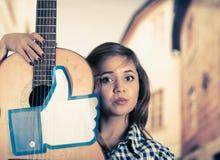 Κουίτο, Ισημερινός - 11 Μαρτίου 2016: Σοβαρή γυναίκα που κρατά μια κιθάρα με έναν μεγάλο όπως το χέρι που τυπώνεται, σε μια θολωμ Στοκ Εικόνες