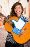 Κουίτο, Ισημερινός - 11 Μαρτίου 2016: Χαμογελώντας γυναίκα που κρατά μια κιθάρα με έναν μεγάλο όπως το χέρι που τυπώνεται, σε μια Στοκ Εικόνα