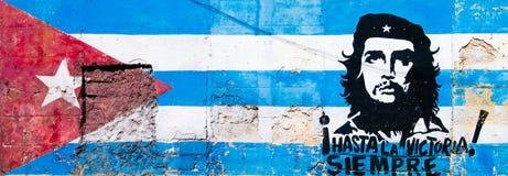Κουβανικά σημαία και Che Guevara που χρωματίζεται στον παλαιό τοίχο σε Havan στοκ εικόνες
