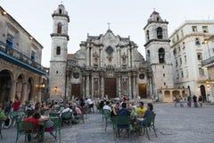 Κουβανοί και οι τουρίστες που κάθονται στους πίνακες διασκόρπισαν Plaza de Λα Catedral σε παλαιό Havan Στοκ Φωτογραφία