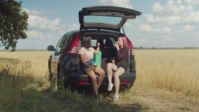 Κουβεντιάζοντας γυναίκα με τη συνεδρίαση καφέ στον κορμό αυτοκινήτων απόθεμα βίντεο