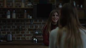 Κουβεντιάζοντας κορίτσια που απολαμβάνουν το ζεστό ποτό στην κουζίνα απόθεμα βίντεο