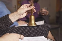 Κουδούνι χαλκού στα χέρια μιας γυναίκας σε μια συνεδρίαση ή ένα σεμινάριο στοκ εικόνες