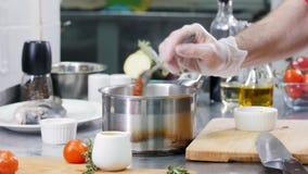Κουζίνα εστιατορίων Αρχιμάγειρας που προσθέτει μια παχιά σάλτσα στη σούπα απόθεμα βίντεο