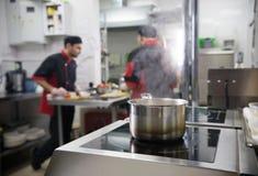 Κουζίνα εστιατορίων Δύο άτομα που εργάζονται στην κουζίνα Τρόφιμα που βράζουν στο πιάτο στοκ εικόνες