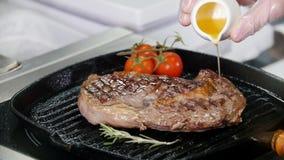 Κουζίνα εστιατορίων Κομμάτι τηγανίσματος αρχιμαγείρων της μπριζόλας στο τηγάνι Προσθήκη ενός χυμού στην κορυφή απόθεμα βίντεο