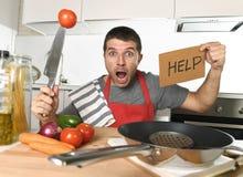 Κουζίνα νεαρών άνδρων στο σπίτι στην ποδιά μαγείρων απελπισμένη στην πίεση μαγειρέματος Στοκ Φωτογραφία