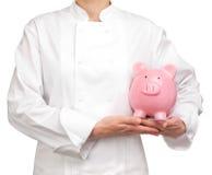 Κουζίνα που κρατά μια piggy τράπεζα Στοκ φωτογραφίες με δικαίωμα ελεύθερης χρήσης
