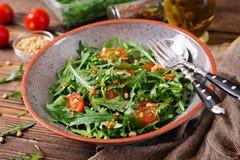 Κουζίνα Vegan Υγιής σαλάτα με το arugula, τις ντομάτες και τα καρύδια πεύκων Στοκ φωτογραφία με δικαίωμα ελεύθερης χρήσης
