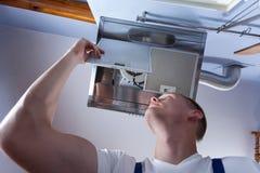 Κουκούλα τοίχων κουζινών καθορισμού Handyman στοκ εικόνα