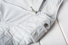 Κουμπί αγκραφών μετάλλων στο άσπρο σακάκι δέρματος Στοκ εικόνες με δικαίωμα ελεύθερης χρήσης