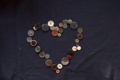 Κουμπί για το ράψιμο υπό μορφή καρδιάς σε ένα μπλε ύφασμα Στοκ Εικόνες