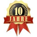 Κουμπί ιωβηλαίου με το έμβλημα και κορδέλλες για 10 έτη Στοκ Εικόνα