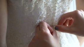 Κουμπί παράνυμφων επάνω στα κουμπιά στο φόρεμα νυφών φιλμ μικρού μήκους