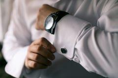 Κουμπιά ατόμων στις μανσέτες χεριών στο ρολόι Στοκ φωτογραφία με δικαίωμα ελεύθερης χρήσης
